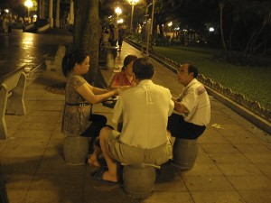 Three middle aged men and one woman sit around a square table in a park. It is night' there are lights on along the paved path in the background.