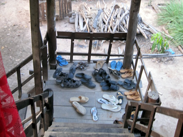 A flight of wooden stairs; on the landing are about a dozen pairs of shoes. The staircase appears to be outdoors; there are bushes in the background.